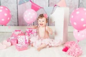 בת שנה בצילומי יום הולדת מרגשים עם מתנות ובלונים ורודים