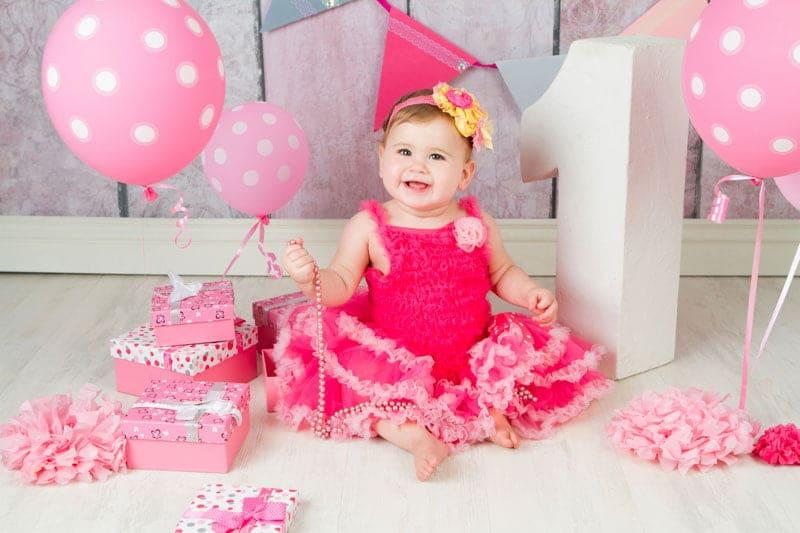 צילומי יום הולדת לילדה בת שנה עם שמלה ורודה ובלונים