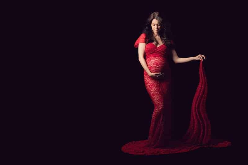 צילומי הריון להילה שמחזיקה שובל שמלה אדומה תחרה