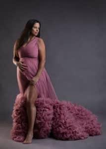 תמונה של קרן בצילומי הריון עם שמלה ורודה על רקע אפור