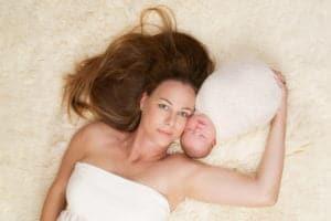 צילומי ניובורן של תינוקת עם אמה על רקע פרווה לבנה