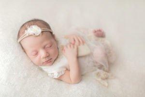 צילום ניובורן לתינוקת עם סרט ראש לבן מחזיקה לב