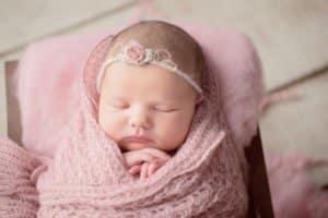 צילום ניובורן לתינוקת עטופה בורוד עם סרט ראש ורוד