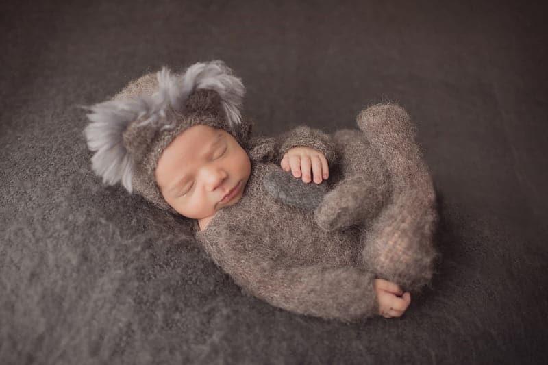 צילומי ניו בורן לתינוק בבגד מצמר וכובע קואלה אפור