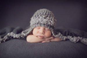 צילומי ניו בורן לתינוק בן שבוע עם רקע אפור וכובע אפור תואם