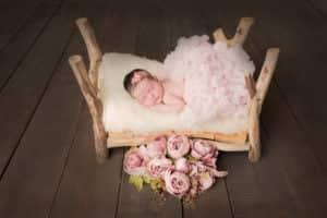 תינוקת בת שבוע ישנה במיטה מעץ בזמן צילומי ניובורן
