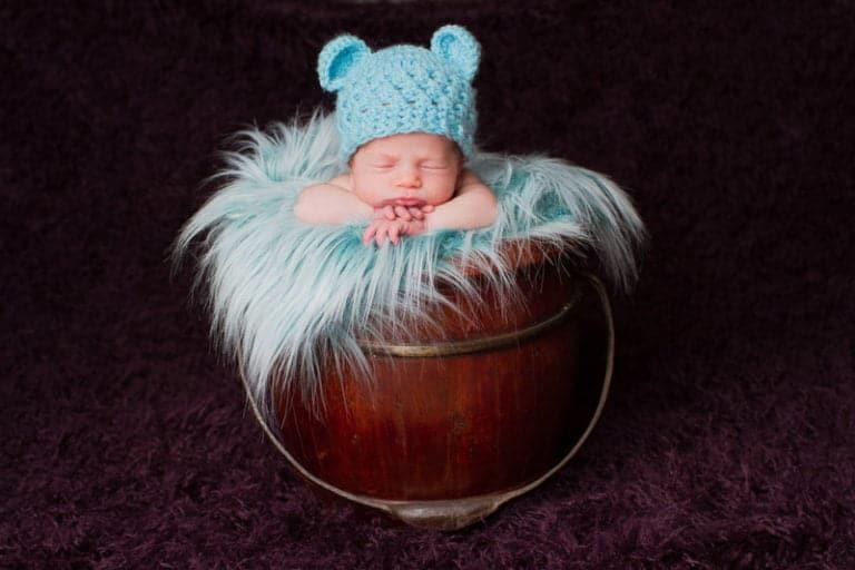 צילום ניובורן לתינוק בן שבוע שמונח בסלסלת עץ עם פרווה רכה וכובע דובון תכלת