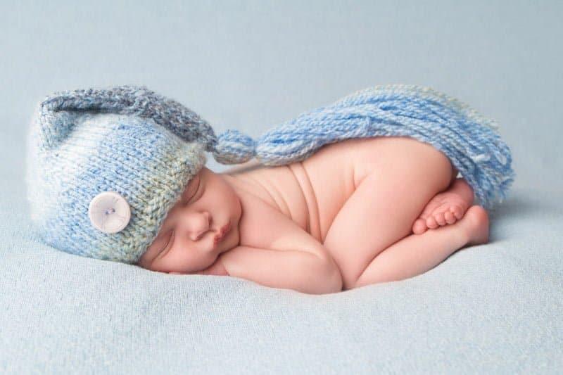 צילום ניובורן על רקע תכלת עם כובע גמדים תואם בסטודיו יעל אלעד
