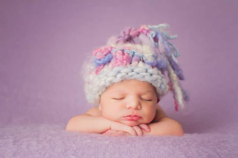 צילום ניובורן לתינוקת על שמיכה סגולה עם כובע סגול וורוד