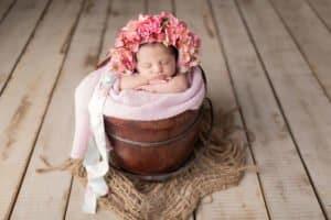 תינוקת ישנה עם כובע פרחים בזמן צילום ניובורן