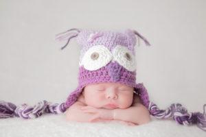 תינוקת מצולמת עם כובע ינשוף סגול