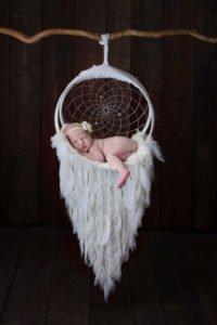 תינוקת קטנטנה מצטלמת על לוכד חלומות לבן