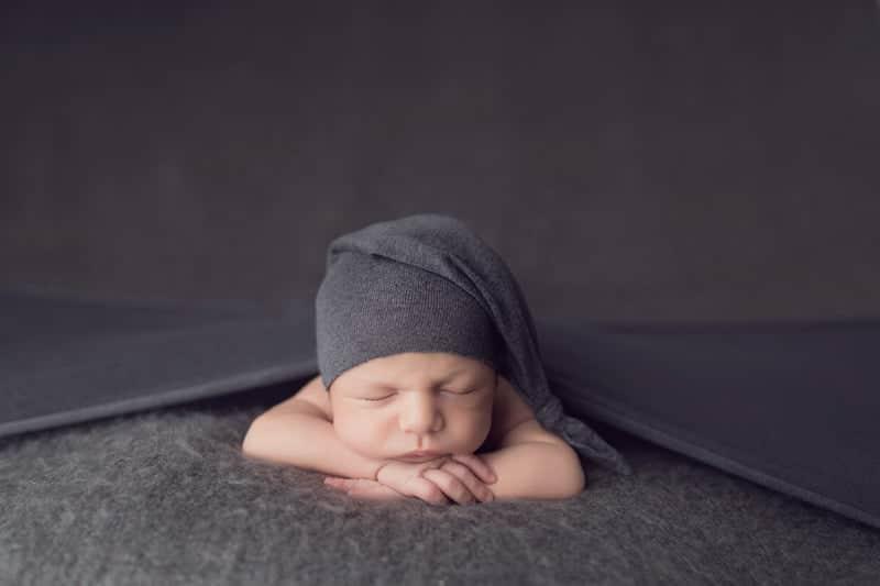 צילום ניובורן לתינוק שרק נולד עם כובע אפור