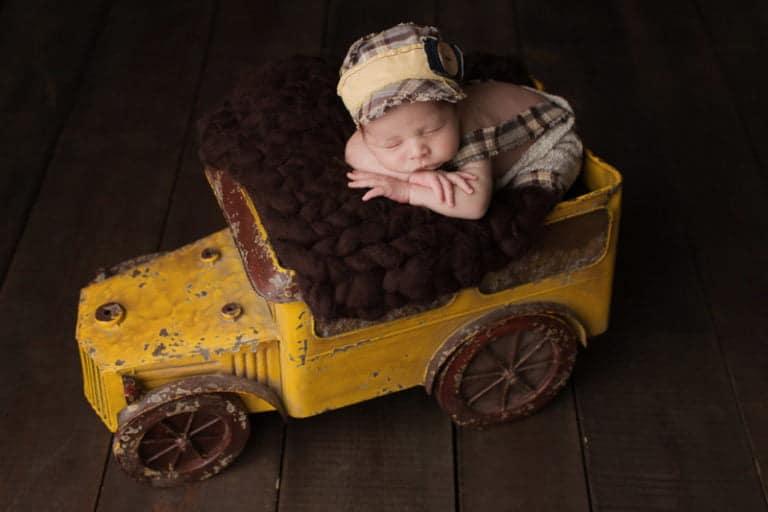 תמונה של תינוק ישן בתוך משאית צהובה בזמן צילומי ניובורן