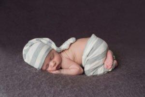 צילום ניובורן לתינוק עם מכנס אפור וכובע אפור