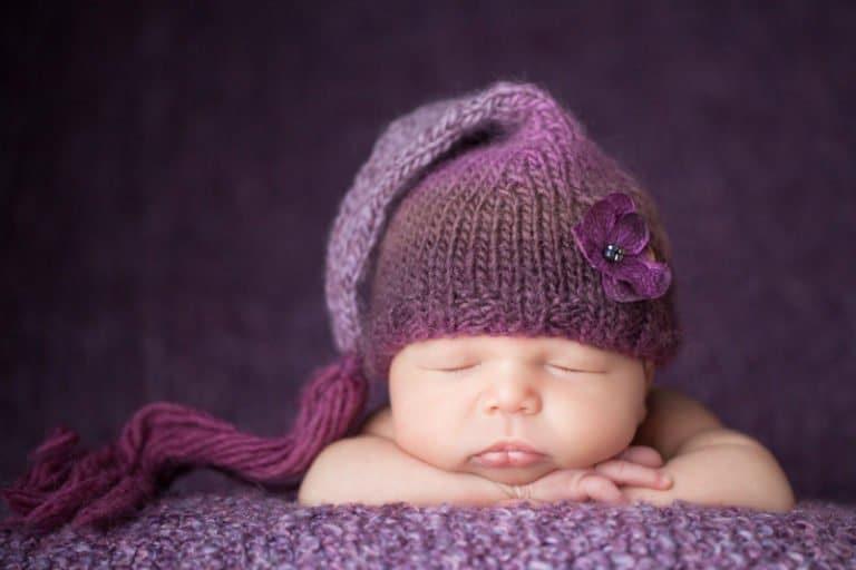 תמונה של תינוקת על רקע סגול עם כובע סגול בצילום ניו בורן