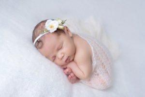 תמונה של תינוקת ישנה בנעימים בעיטוף לבן וסרט ראש לבן