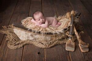 תמונה של תינוק מצולם בסירה על רקע חום