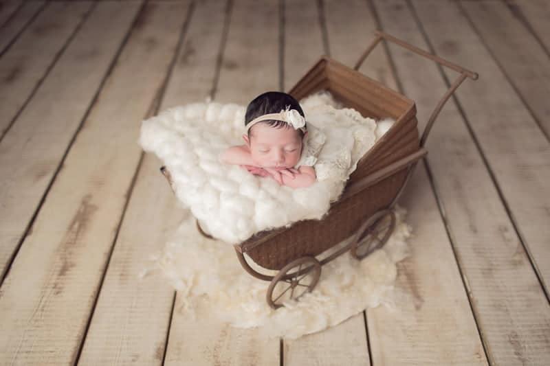 תינוקת בת חמישה ימים ישנה בעגלת וינטג׳ עם שמיכה לבנה בזמן צילומי ניובורן בסטודיו יעל אלעד