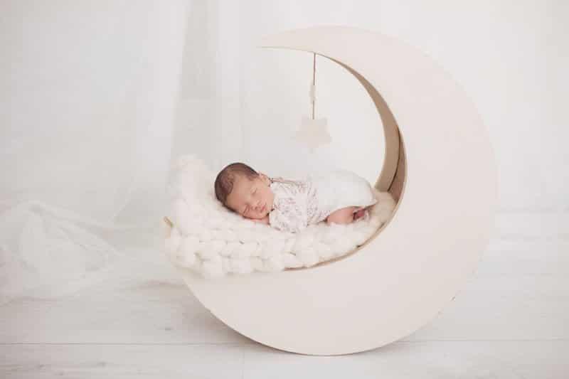 צילומי ניובורן לתינוקת שרק נולדה עם בגד לבן ישנה על הירח