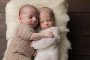 תינוק ותינוקת שרק נולדו מחבקים אחד את השניה במהלך צילומי ניו בורן