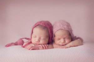 תאומות בצילום ניובורן בסטודיו עם כובעים תואמים