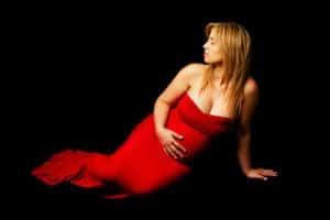 אדר עם שמלה אדומה במהלך צילומי הריון בסטודיו
