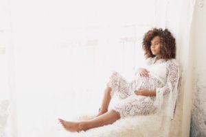 שירלי לבושה בחלוק תחרה לבן בזמן צילום הריון בתאורה טבעית