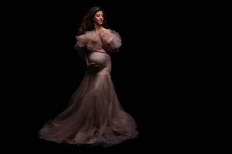 צילומי הריון לנליה על רקע שחור עם שמלת הריון מועצבת בורוד עתיק