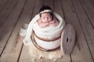 תינוקת קטנטנה בצילומי ניו בורן בשימוש דלי